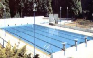 Yarı olimpik, 4 kulvarlı açık bir yüzme havuzunun fotoğrafı Fotoğrafta ; yarışçı yüzücülerin atlama taşları , tabanında kulvar çizgileri ve üstten taşma kanal ızgaraları görünmektedir.